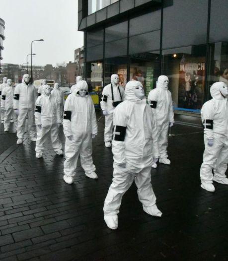Mysterieus ogend gezelschap demonstreert op Van Heekplein in Enschede