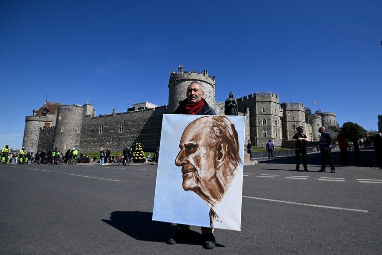 Een kunstenaar houdt een portret van de hertog van Edinburgh buiten Windsor Castle op 17 april 2021 in Windsor, Engeland. De hertog van Edinburgh reisde veel tijdens zijn dienst bij de Koninklijke Marine. Beeld Getty Images