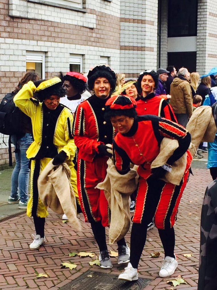 Pieten in gele, rode en blauwe pakken delen pepernoten uit Beeld Geertje Visser