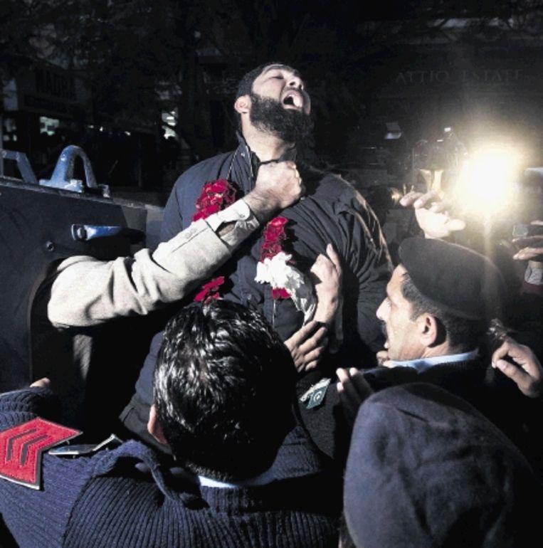 Lijfwacht Mumtaz Qadri roept religieuze teksten terwijl agenten in Islamabad hem wegvoeren. ( FOTO REUTERS ) Beeld REUTERS