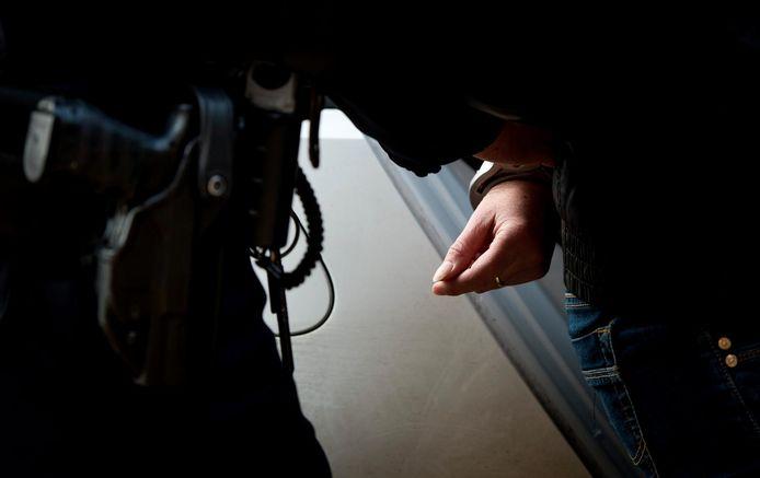 Een politieagenten voert een verdachte af.