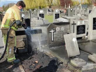 Houten kruis van graf vat vuur op kerkhof