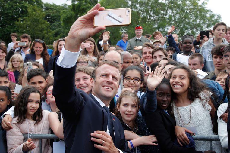 Emmanuel Macron neemt een selfie met het aanwezige publiek tijdens een ceremonie ter ere van de oproep van Generaal Charles de Gaulle tot verzet tijdens WOII.