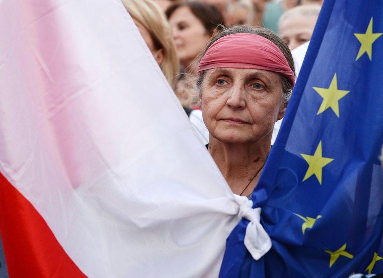 Een demonstrant houdt de vlaggen van Polen en de EU bij elkaar tijdens protesten voor het hooggerechtshof in Warschau op 4 juli. Beeld AP