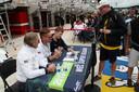 De Nederlandse coureur Renger van der Zande (midden) signeert het fotoboek van Kortland (rechts).
