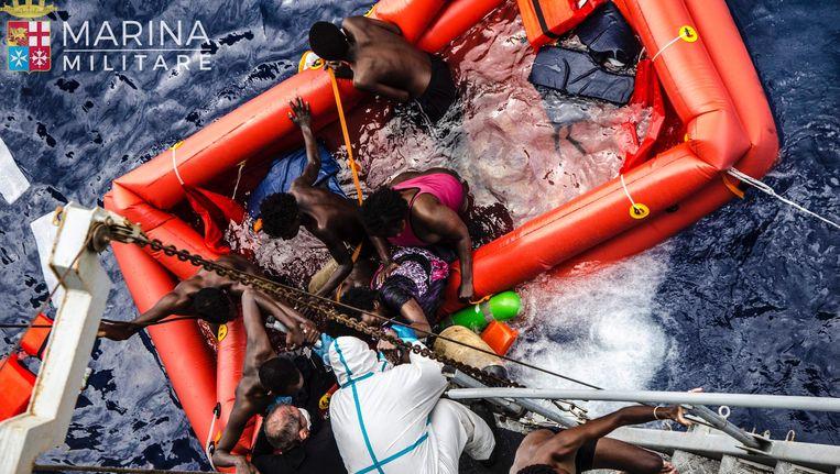 Reddingswerkers helpen migranten aan boord van het Italiaanse marineschip Vega. Beeld ap