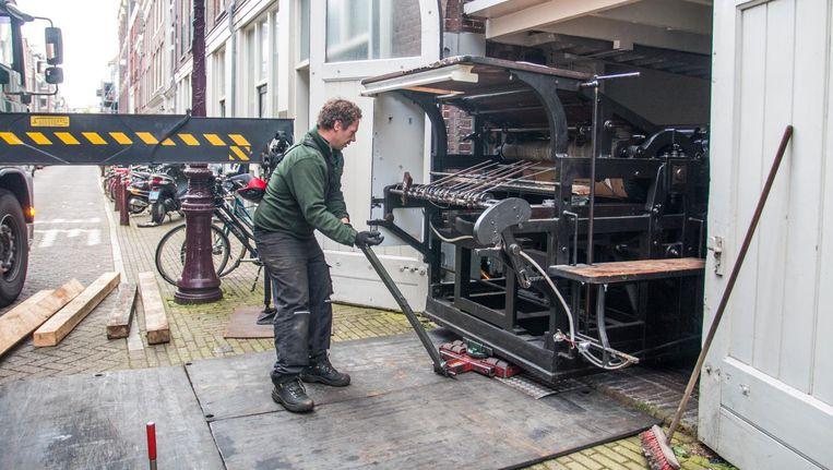 De drukpers, een gietijzeren bakbeest van vijf ton, verlaat de drukkerij in de Utrechtsedwarsstraat. Beeld Jesper Boot