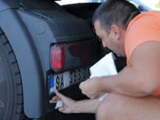Wie de grens tussen Kosovo en Servië overgaat, krijgt stickers om nationale symbolen af te plakken