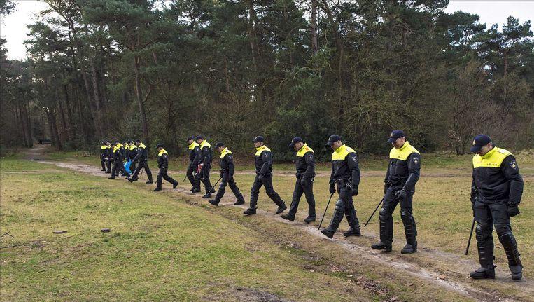 Leden van de Mobiele Eenheid (ME) zoeken in het Heidepark, het bosperceel achter de woning van de overleden Els Borst, naar mogelijke sporen rond de dood van de oud-minister. Beeld epa