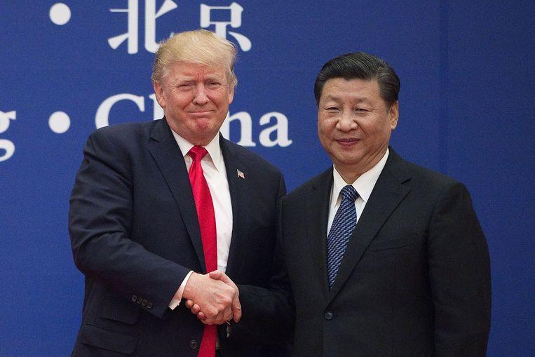 Amerikaans president Trump en zijn Chinese evenknie Xi Jinping schudden elkaar de hand op een zakentop in november 2017. Beeld AFP