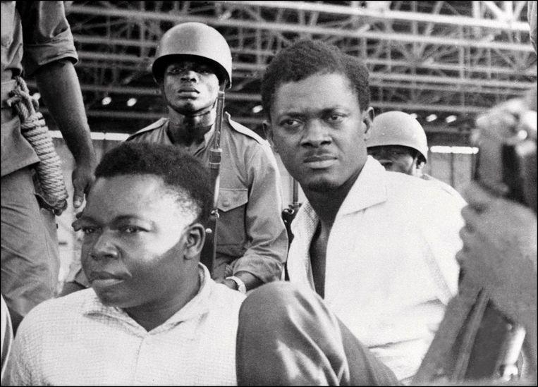 1 november 1960: soldaten bewaken Patrice Lumumba (r.), premier van Congo, en Joseph Okito (l.), vicevoorzitter van de Senaat, na hun arrestatie. Beiden worden later vermoord. Beeld AFP