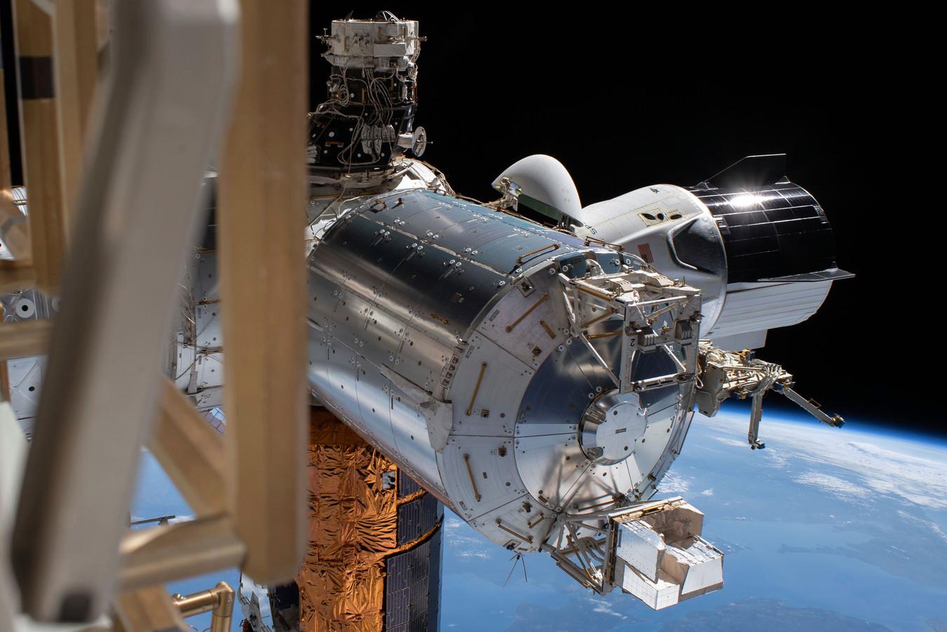 De SpaceX Crew Dragon, rechts, aan het ISS.