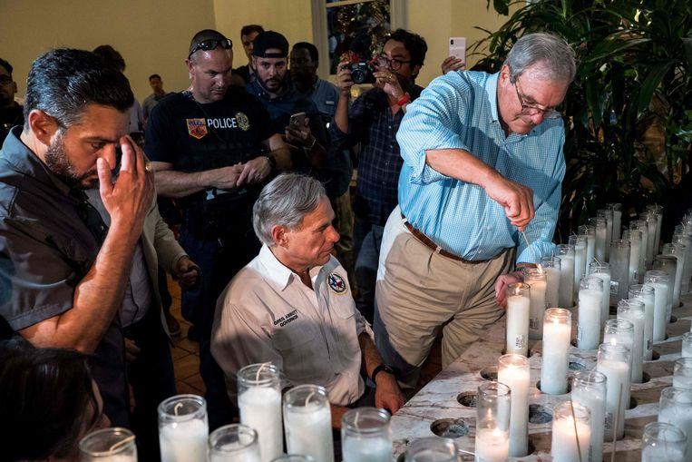 Burgemeester Dee Margo (rechts) steekt een kaars aan tijdens een herdenkingsdienst voor de slachtoffers in El Paso, Texas.  Beeld AFP