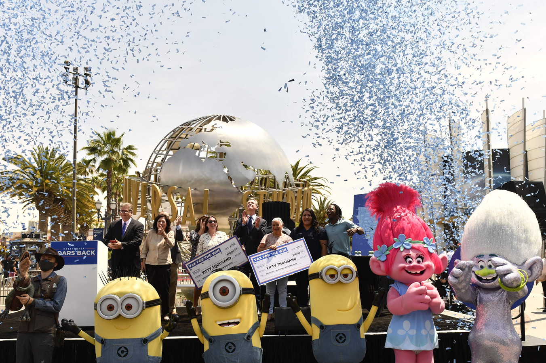 Gouverneur Gavin Newsom (M) van Californië na de overhandiging van symbolische cheques aan winnaars in de Vax For The Win-loterij, op 15 juni in Hollywood.