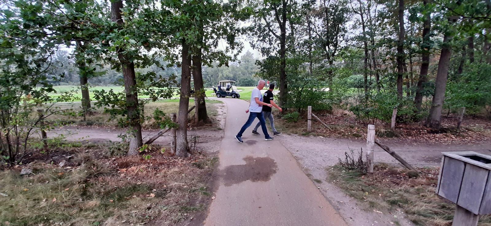 Wandelaars op het openbare pad kruisen op golfbaan The Duke de verharde verbinding tussen de holes 11 en 12.