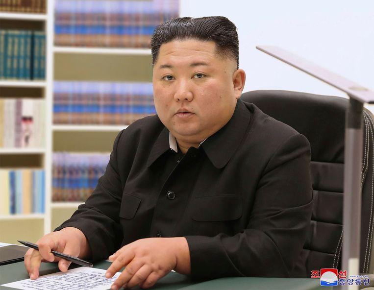 De Noord-Koreaanse leider Kim Jong-un schrijft een nieuwjaarskaart.  Beeld AP