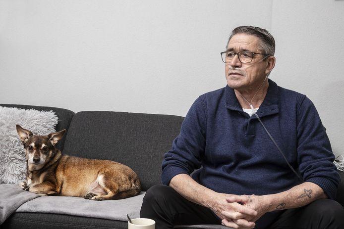 Frans Janssen met hond Russel thuis op de bank.