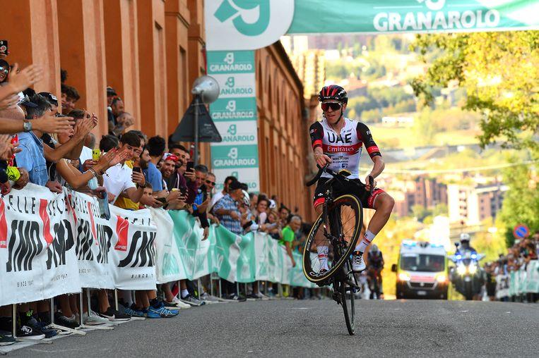 Tadej Pogacar demonstreert zijn macht door eerder deze maand in het Italiaanse San Luca een wheelie te doen. Beeld Getty Images