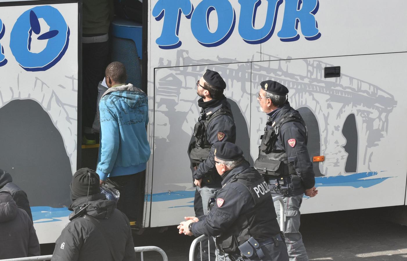 De vluchtelingen gaan in de haven een bus in.