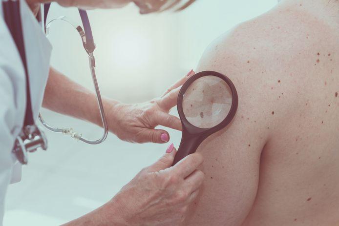 Een huidarts bekijkt de arm van een patiënt.