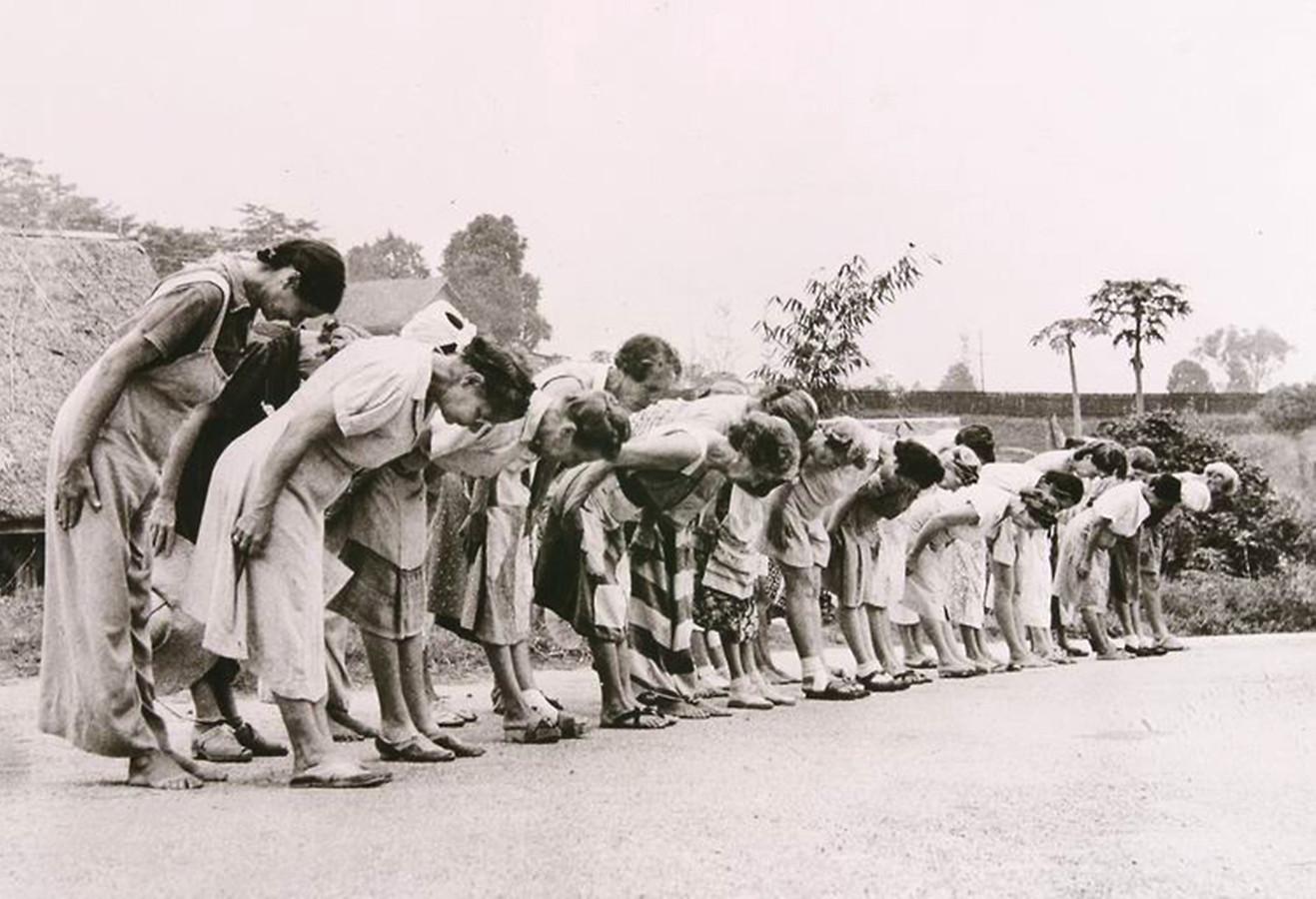 Nederlandse vrouwen in een Jappenkamp moeten de traditionele buiging voor de Japanse keizer maken, Nederlands Indië tijdens de Tweede Wereldoorlog.