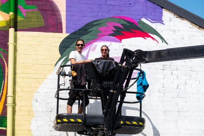 De artiesten Dourone en Elodie aan de kleurrijke gevel.