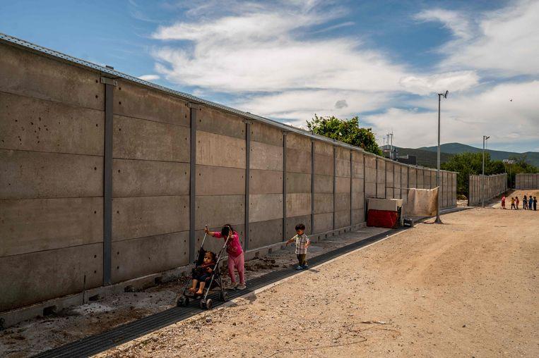 Kinderen spelen bij een de muur rondom vluchtelingenkamp Ritsona, buiten Athene.  Beeld AFP