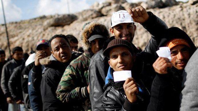 Archieffoto van Tunesische vluchtelingen in de rij voor toegang tot een boot die ze van het overvolle Lampedusa naar een ander deel van Italië brengt.
