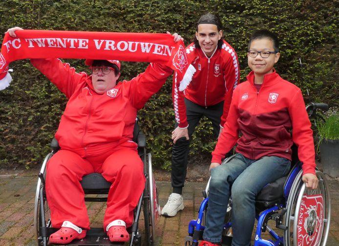 Timo Mentink en Linda Bakker zijn in hun sas met de FC Twente-schermen voor hun rolstoel, die Ramiz Zerrouki ze aanbiedt.