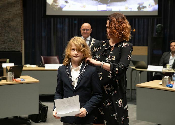 Moeder Jettie hangt zoon Rens Klaassen de ambtsketen om. Op de achtergrond burgemeester Kees van Rooij.