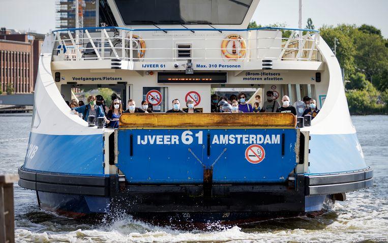 Reizigers met mondkapjes bij de pont achter Amsterdam CS.  Beeld Hollandse Hoogte /  ANP
