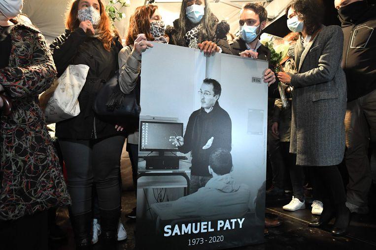 Nabestaanden en collega's houden een foto vast van de vermoorde geschiedenisleraar Samuel Paty.  Beeld AFP