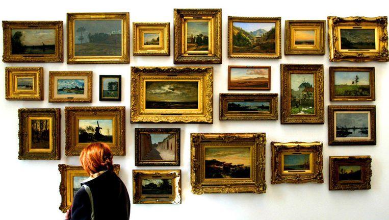Een bezoeker van het Boijmans Van Beuningen museum in Rotterdam staat zondag voor een collectie landschaps schilderijen (Plein-air) uit de 17e eeuw. Beeld ANP