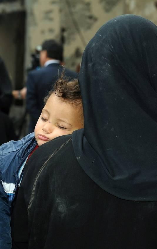 Een vluchtelingen en haar kind in de rij voor voedsel in Yarmouk.