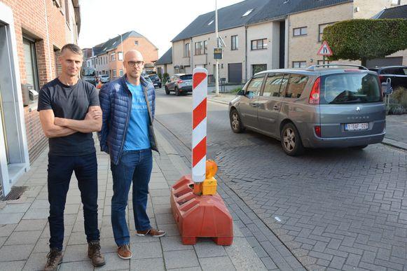 Buurtbewoners Luc De Kimpe en Stefaan De Meulder bij de obstakels die maandag op het voetpad werden geplaatst zodat auto's geen fietsers via het voetpad meer voorbij kunnen rijden.