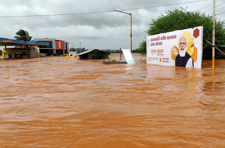 Een billboard met premier Narenda Modi staat onder water in Kolhapur in de regio Maharashtra. Duizend mensen werden al gered bij de overstromingen.  Beeld AP