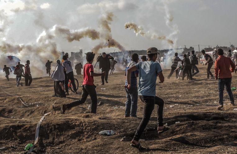 Palestijnse demonstranten gaan op de loop voor Israëlisch traangas tijdens de bloedige protesten van maandag.  Beeld EPA