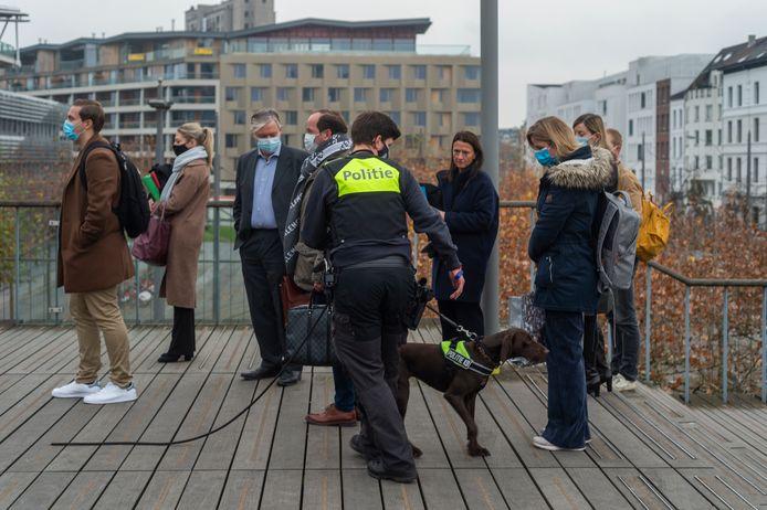 Politie controleert de bezoekers met explosievenhonden voor zij het justitiepaleis binnengaan.
