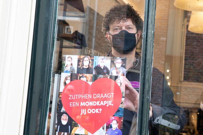 Martijn Droog, eigenaar van notenzaak Noten & Zo, plakt een poster op zijn etalage. Winkeliers in Zutphen roepen bezoekers ermee op mondkapjes te dragen in de winkel.