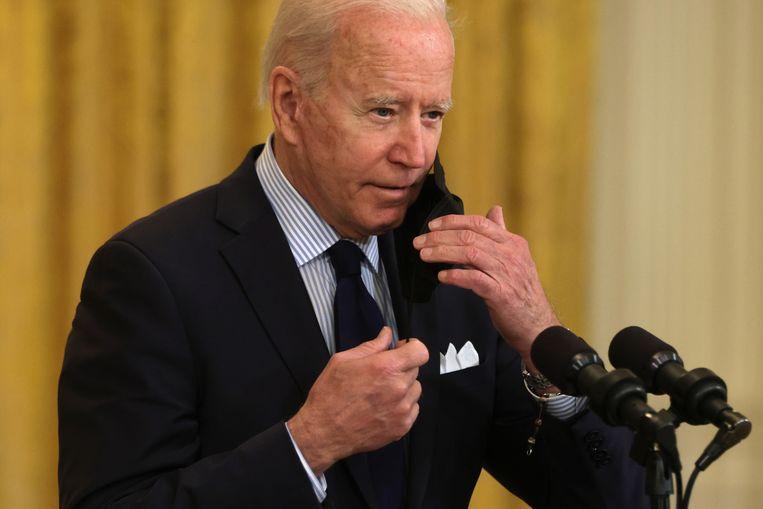 Amerikaans president Joe Biden zet zijn mondmasker af. Beeld Getty Images