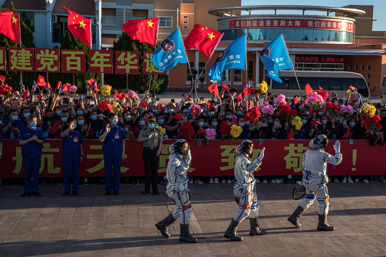 De Chinese astronauten Tang Hongbo, Nie Haisheng, en Liu Boming zwaaien tijdens een vertrekceremonie voorafgaande aan hun ruimtevlucht naar het Hemels Paleis 'Tiangong', het eerste echte ruimtestation van het land.