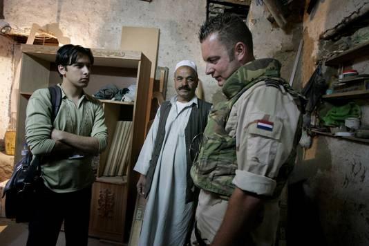 Een Nederlandse militair onderhandelt via een tolk (links) met een Afghaanse timmerman.