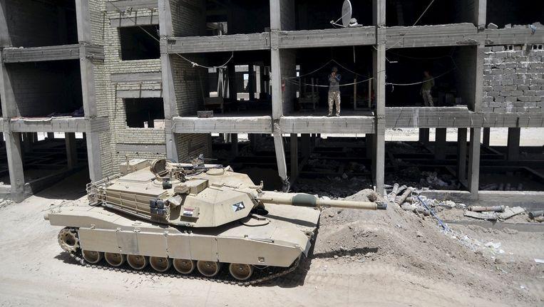 Een tank van het Iraakse leger in een buitenwijk van Falluja. Beeld reuters