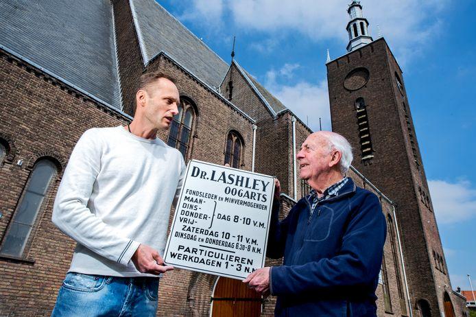 Het originele bordje van de praktijk van dr. Lashley werd een paar jaar geleden aan Henk den Haan (r.) van de Breepleinkerk overhandigd. Gulle gever was Schiedammer Michael Hendriks.