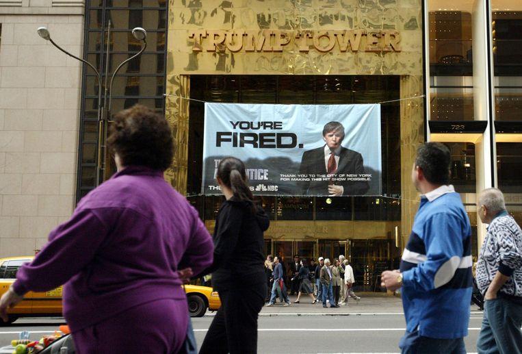 Voorbijgangers aanschouwen anno 2004 een grote The Apprentice-banner aan de Trump Tower in New York. Beeld AP