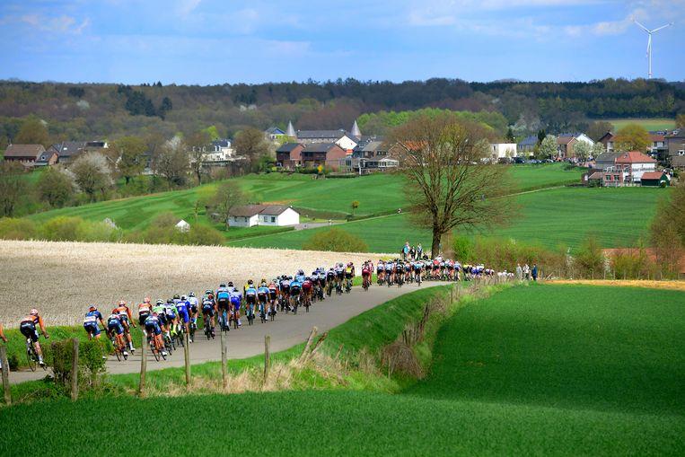 Het peloton dendert over de glooiende wegen van Nederlands-Limburg. Beeld Photo News