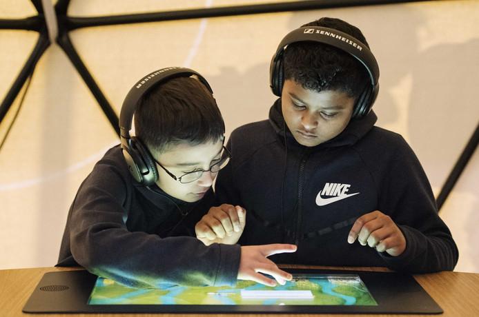 De 10-jarige Arda (l) en Shivano spelen in de Shell-tent. Werken bij een raffinaderij noemen zij nu 'een optie'.