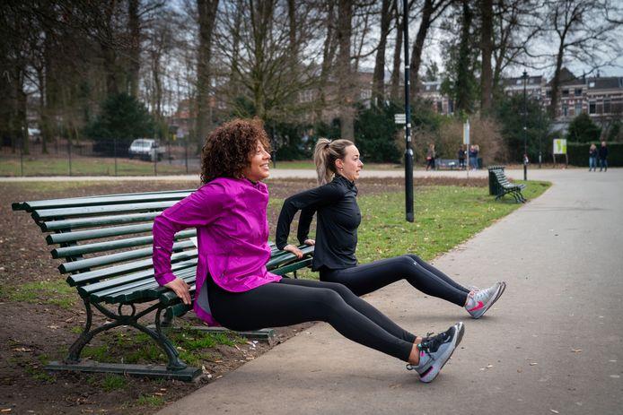Sabine Entingh  (l) en Leonie Wieggers gebruiken een bankje van park Sonsbeek voor hun oefeningen.