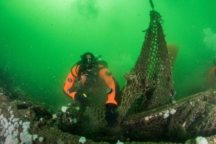 Een duiker van stichting Ghost Fishing ontdoet het scheepswrak van het ooit door de Duitsers getorpedeerde SS Trevier van vistuig.
