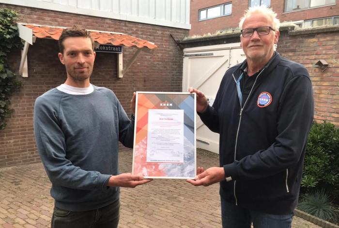 De uit het water geredde Ruurd (links) overhandigt een oorkonde aan Arie Verbaan (rechts) van de KNRM Scheveningen.